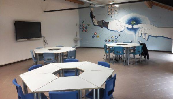 Tavoli trapezoidali nell'aula laboratorio, con il nuovo murales